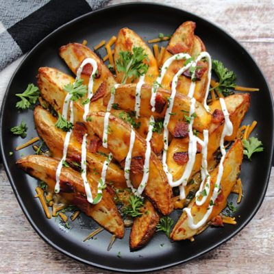 black plate with loaded potato wedges