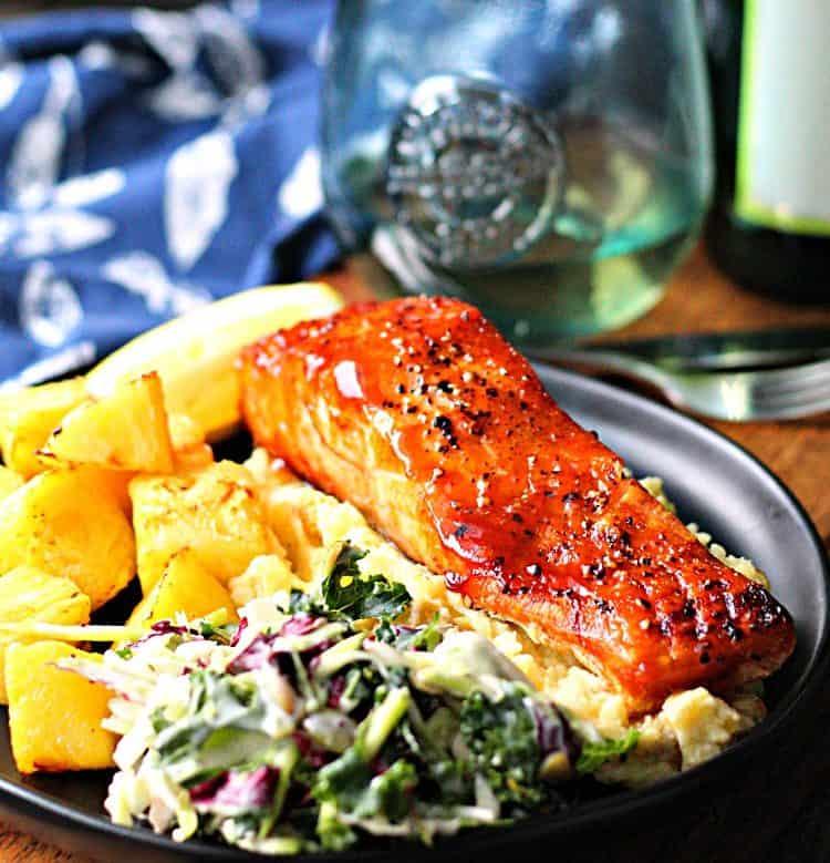 black plate with teriyaki salmon, slaw and pineapple cubes.