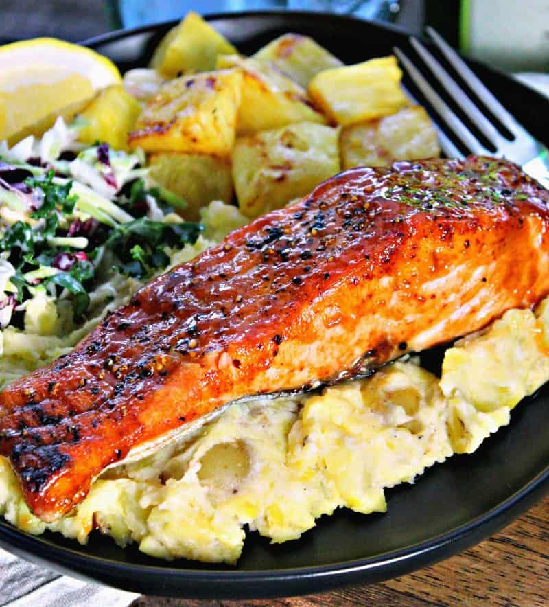 plate with air fryer teriyaki salmon filet with slaw and pineapple chunks