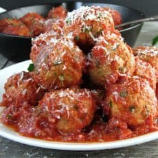 meatballs in marinara piled high on a white plate