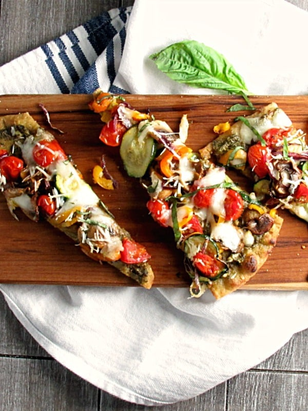 Veggie Flatbread Pizza on Stonefire naan, topped with pesto, roasted vegetables and cheese. Easy, delicious lunch or dinner.