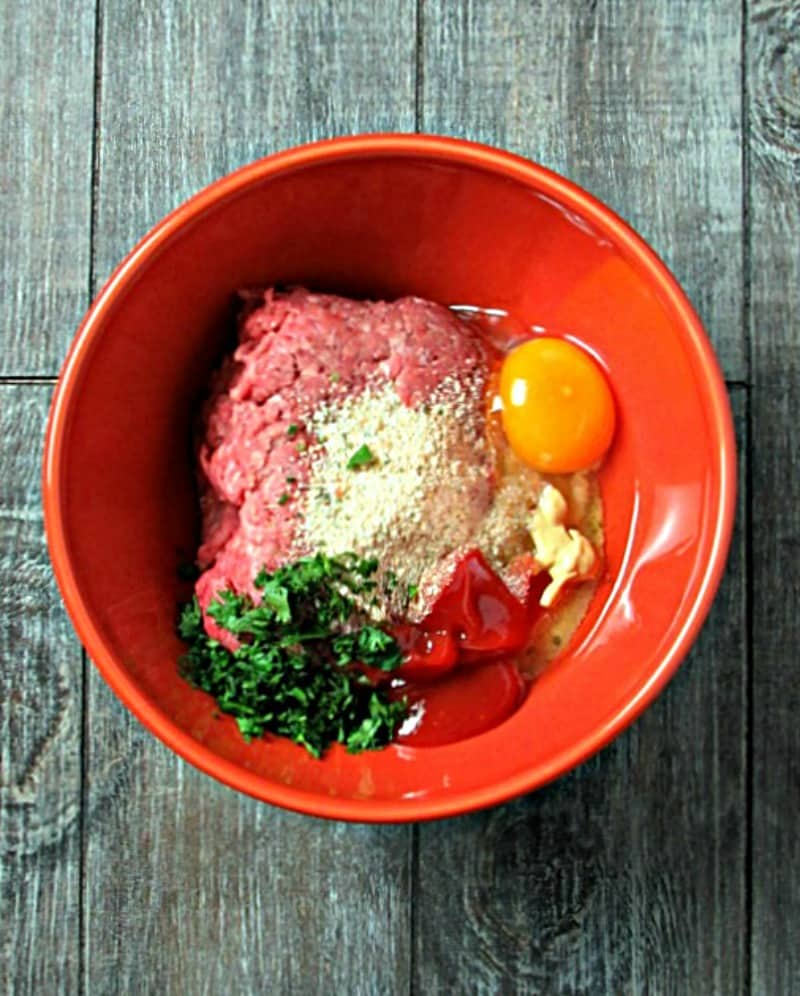 overhead view of ground beef, egg and other ingredients in a bowl before blending
