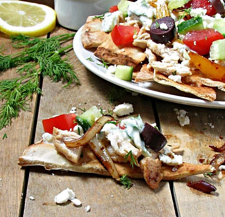 Greek Chicken Pita Nachos. Warm, toasted pita chips layered with seasoned chicken, Tzatziki, sauteed peppers and onions, tomatoes, cucumbers and feta cheese.