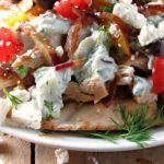 Greek Chicken Pita Nacho. Warm, toasted pita chips layered with seasoned chicken, Tzatziki, sauteed peppers and onions, tomatoes, cucumbers and feta cheese.