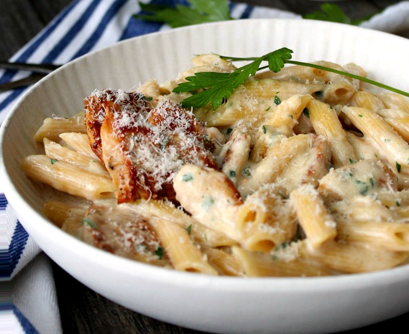 bowl of chicken alfredo garnished with chopped parsley and grated parm