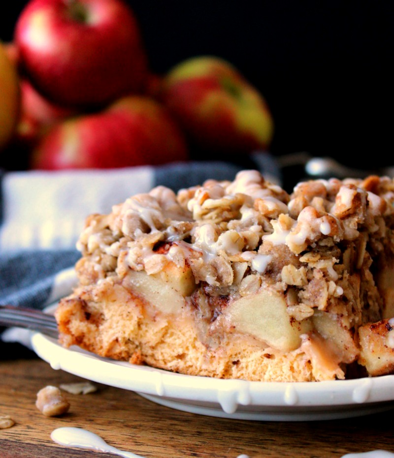 wedge of cinnamon roll apple crisp on white plate with bowl of red apples in background