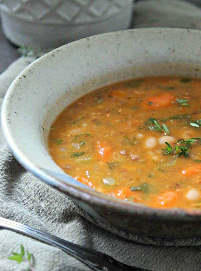 bean with bacon soup ~ bowl of soup garnished with fresh thyme