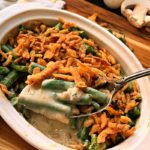 white casserole dish with small batch of green bean casserole topped with crispy onions