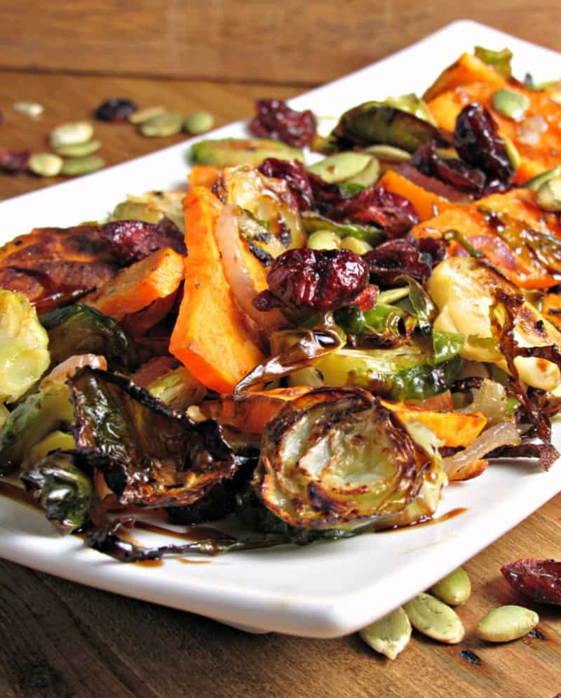 roasted vegetables on white plate topped with cranberries and pepitas