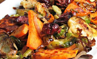 Caramelized Brussels Sprouts Sweet Potato Medley: delicious roasted veggies drizzled with balsamic glaze and topped with dried cranberries & pepitas.