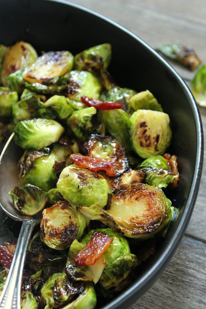 black bowl with caramelized brussels sprouts halves and bacon pieces
