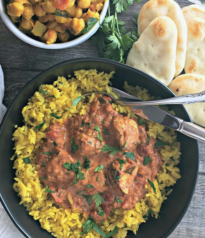 butter chicken recipe ~ overhead photo served with yellow jasmine rice and a side of chickpeas