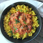 butter chicken recipe ~ overhead photo of yellow tumeric indian style rice topped with creamy butter chicken. serve with any rice or naan bread
