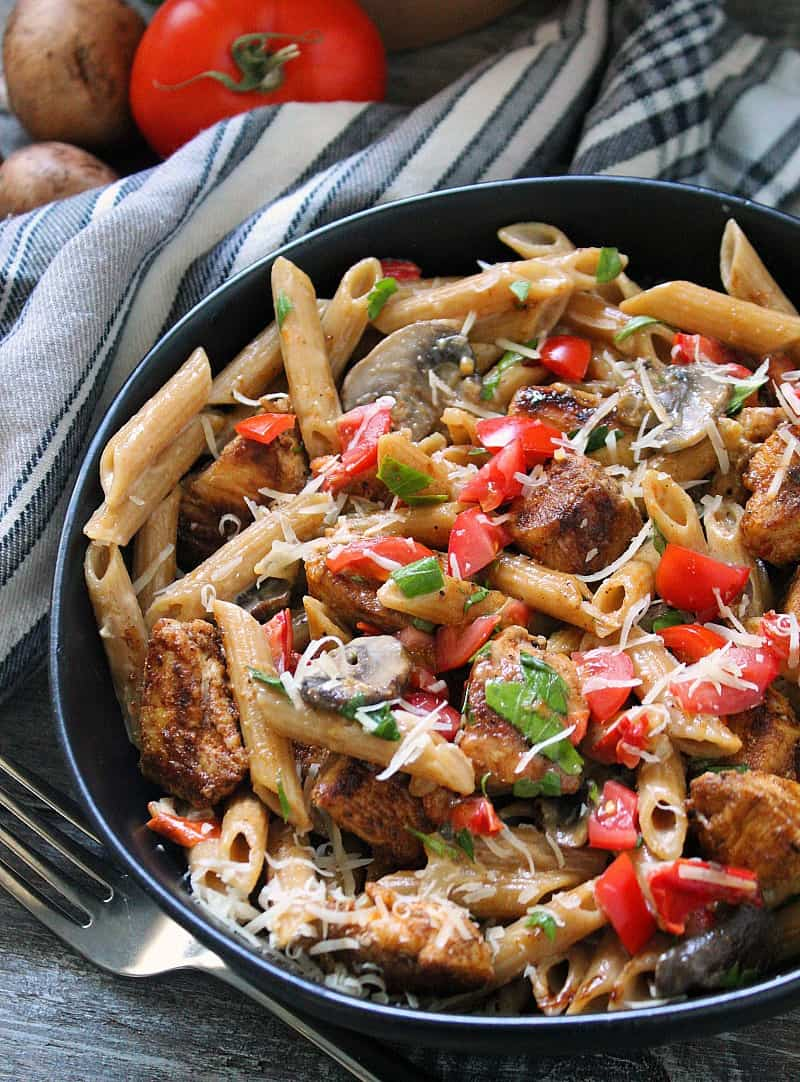 creamy cajun chicken pasta ~ cajun seasoned chicken bites, penne pasta, mushrooms, bell peppers in a creamy spicy alfredo sauce garnished with diced tomatoes.