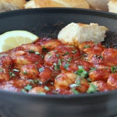 spicy new orleans style shrimp ~ cooked shrimp in spicy sauce in the skillet plus lemon wedge and crusty bread.