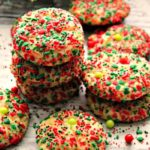 red and green sprinkled cookies stacked on a white board