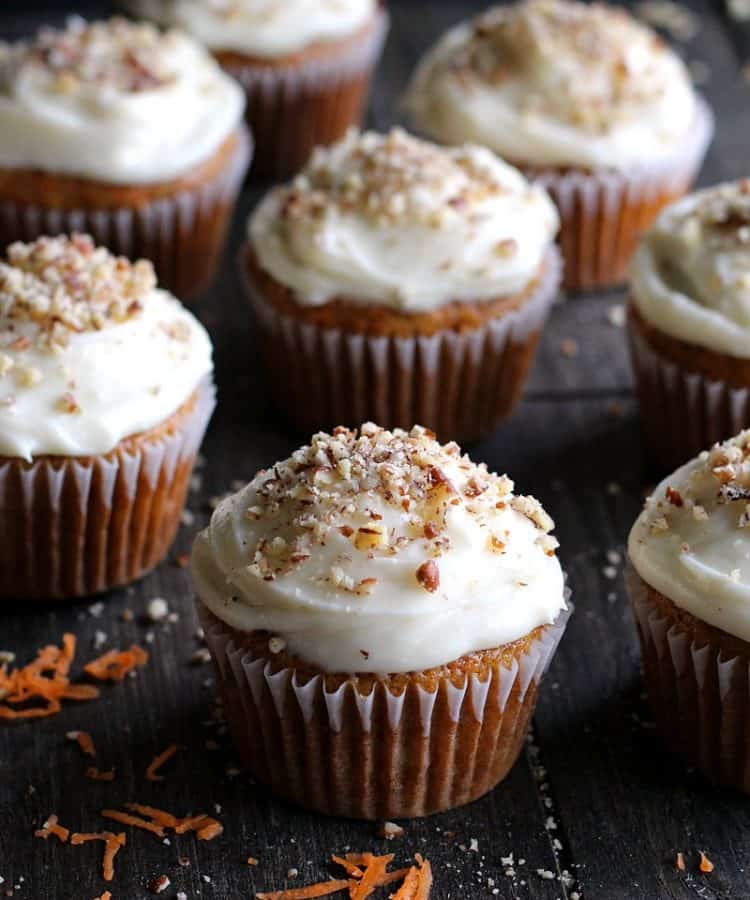 carrot cake cupcakes ~ easy recipe from scratch shows cream cheese frosted cupcakes sprinkled with finely chopped pecans.