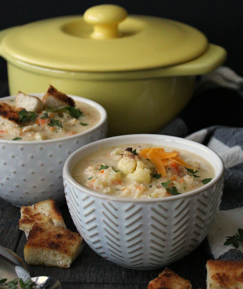 two bowls of roasted cauliflower soup topped with grated cheese