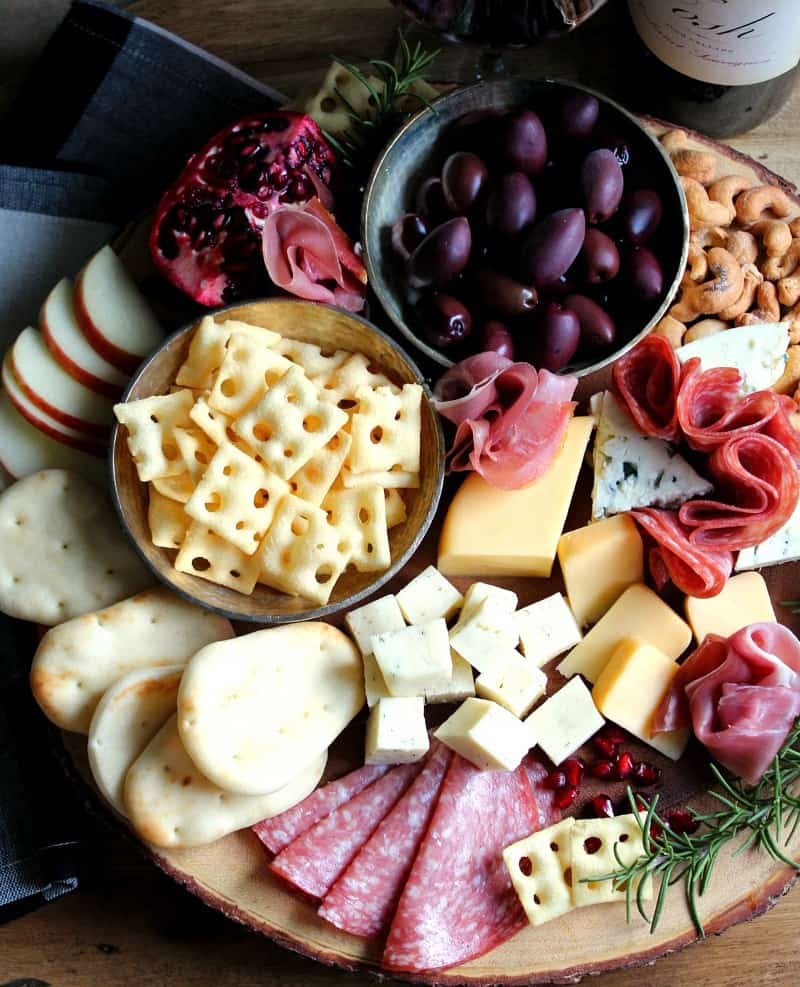 A display of meats, cheeses, bread, fruit and nuts on a wood board.