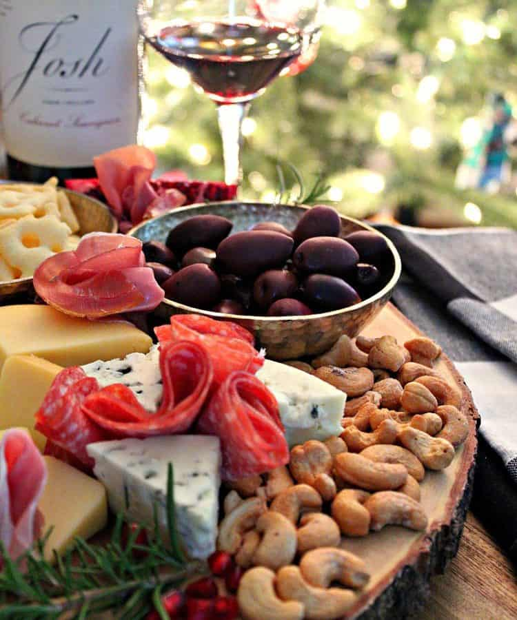 Cheese and Charcuterie Board ~ meats, cheeses, bread, fruit and nuts displayed on a board with wine in the background