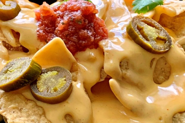 plate of nachos with cheese sauce on top garnished with jalapenos