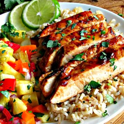 plate of sliced chili lime chicken over brown rice with pineapple salsa on the side