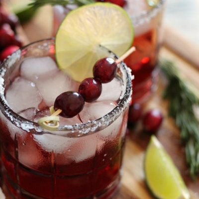2 cranberry christmas margaritas garnished with fresh cranberries, lime slice and fresh cranberries
