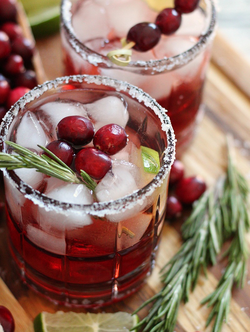 cranberry christmas margaritas in salt rimmed glasses garnished with fresh cranberries
