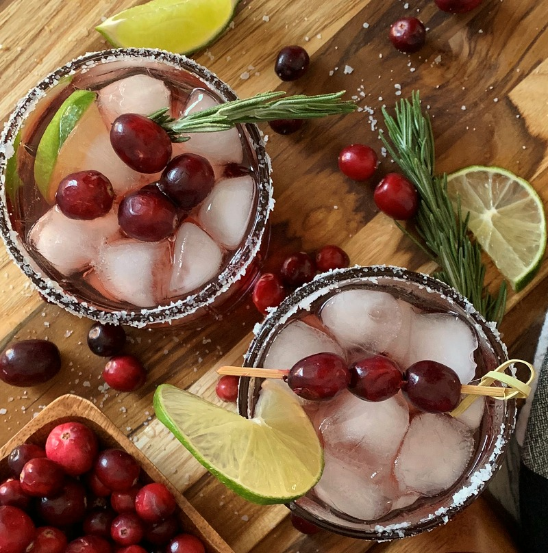 overview view of cranberry christmas margaritas garnished with rosemary sprig and fresh cranberries
