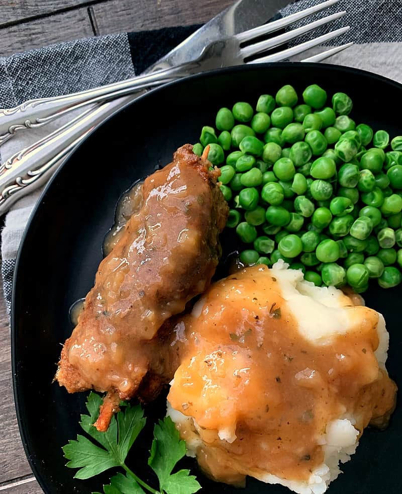 black plate with city chicken and mashed potatoes covered in gravy plus a side of green peas