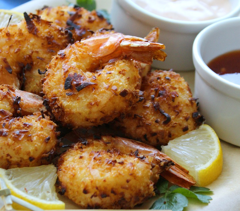white plate with pile of golden coconut shrimp garnished with lemon