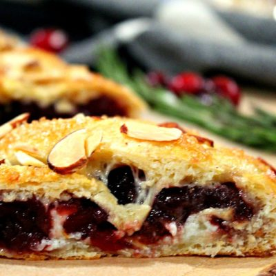 sliced cranberry brie crescent braid garnished with almonds