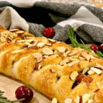 lightly browned cranberry brie crescent braid garnished with almonds