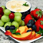 dip in a bowl shown with fresh strawberries, grapes, slices peaches and blueberries