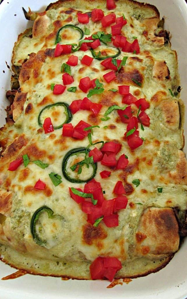 Salsa Verde Enchiladas packed with porkCarnitasOR rotisserie chicken, topped with creamy salsa verde sauce & cheese baked until golden brown.
