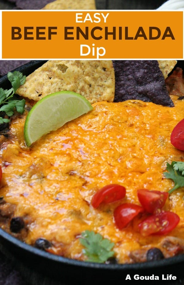 Beef Enchilada Dip pin ~ view of dip topped with melted cheese, garnished with lime wedge, tortilla chips, tomatoes and cilantro.
