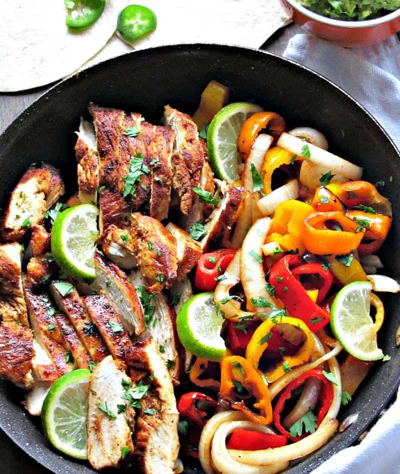 shown in skillet, sliced cooked chicken and bright bell peppers and onions, garnished with lime slices