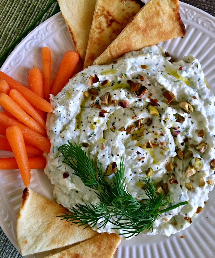 Overhead shot of creamy dip garnished with dill sprig surrounded by pita chips and carrots