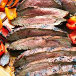 thin sliced grilled flank steak on a cutting board with bright colored grilled bell peppers