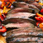 sliced flank steak on a cutting board surrounded by colorful grilled bell peppers