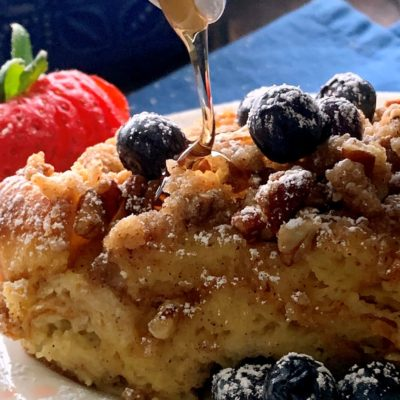 french toast casserole with syrup drizzled on top