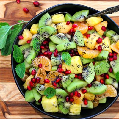 black bowl filled with winter fruit salad of kiwi, pomegranate, mandarin and pineapple