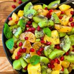 black bowl with winter fruit salad of pineapple, kiwi, mandarins and pomegranate