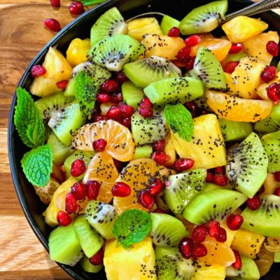 black bowl with winter fruit salad of pineapple, kiwi, mandarins and pomegranate