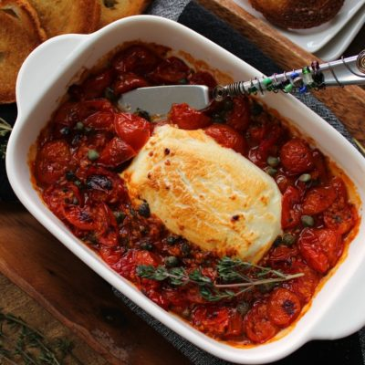 white baking dish with baked goat cheese and roasted tomatoes