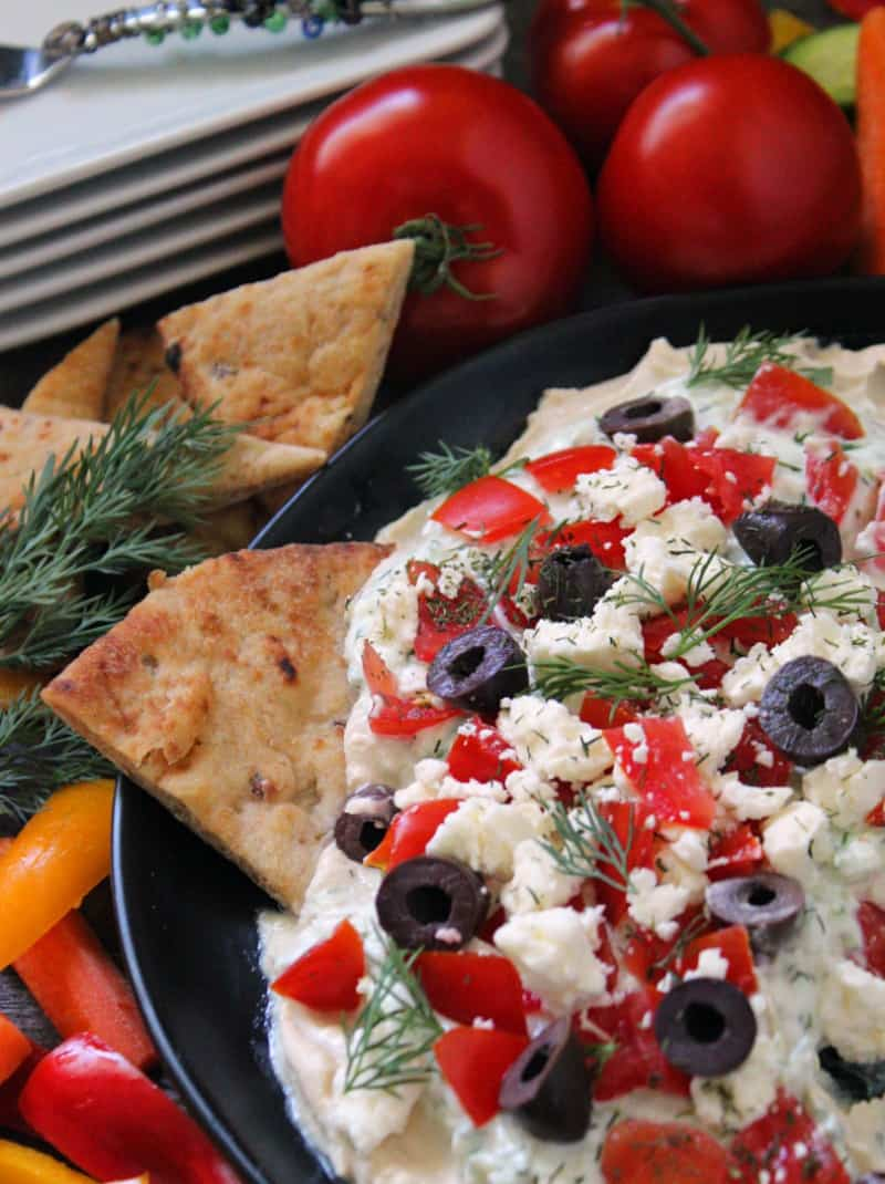layered greek dip shown with pita triangles, fresh tomatoes and white appetizer plates