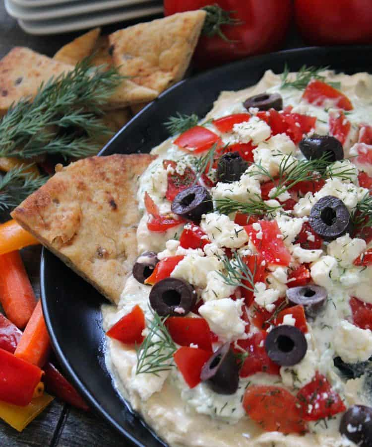 mediterranean dip - layers of hummus,tzatziki, tomatoes and olives garnished with fresh dill and served with pita and vegetables