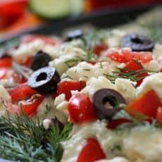 layered greek appetizer of hummus, tzatziki, tomatoes, feta and olives.