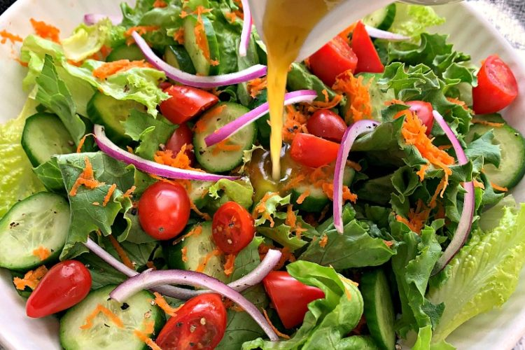 salad in white bowl with dressing poured over the top
