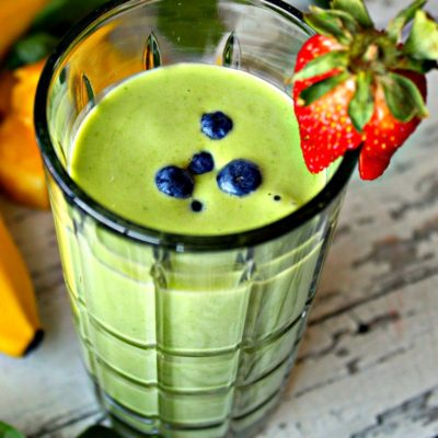 green smoothie in clear glass garnished with blueberries